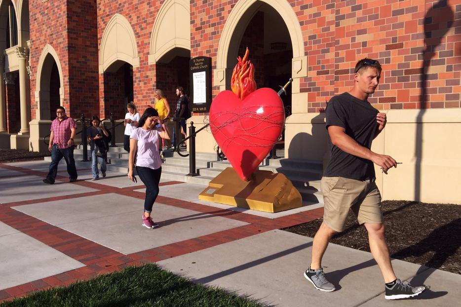 College students walk past a sculpture of the Sacred Heart at St. Thomas Aquinas Church on the University of Nebraska campus in Lincoln.