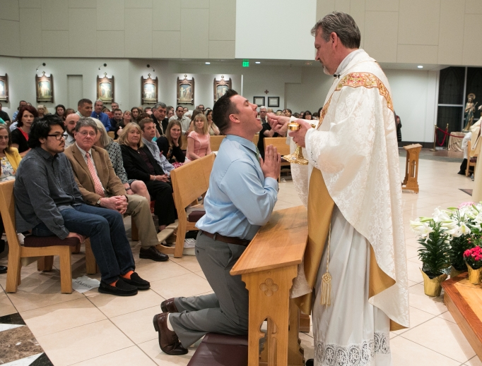 Tanner Rogers receives first Holy Communion at the Easter vigil 2019.