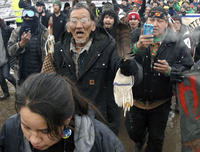 In this 2017, file photo,Nathan Phillips (center with glasses), marches out of the Oceti Sakowin camp before the deadline set for evacuation of the camp near Cannon Ball, North Dakota. Phillips was part of a large crowd representing a majority of the remaining Dakota Access Pipeline protesters, A source close to the leadership of the National Basilica of the Shrine of the Immaculate Conception in Washington corroborated an eyewitness account that saw Phillips and a group of activists tried to enter the church during Mass while playing drums and chanting. They were prohibited from entering the building by security personnel, who locked the main basilica doors with the congregation still inside.