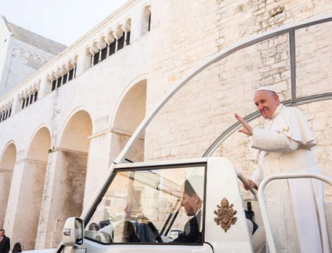 Pope Francis waves from the popemobile in Bari, Italy Feb. 23.