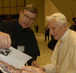Father John Phalen presents a book of Rosary pledge names to Pope Benedict XVI.