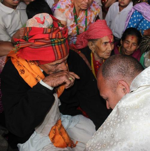 Jesuit Father Tek Raj Paudel kneels before his parents, Indra Bahadur Paudel and Uttra Kumari, during his April 25 ordination Mass in the Nepalese village of Tarkerabari.