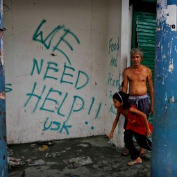 Residents stand next to grafitti requesting aid in the aftermath of Typhoon Haiyan on Nov. 13 in Tacloban, Leyte, Philippines.