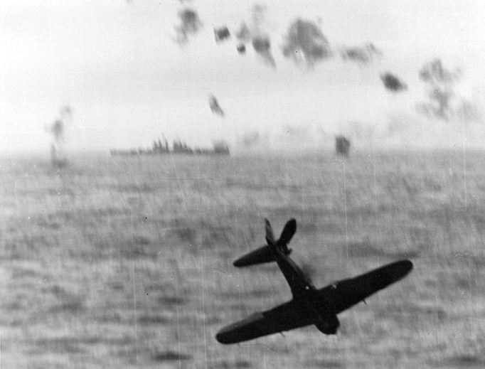 A Japanese Zero Kamikaze crashes into the sea after trying to hit the aircraft carrier USS Essex (CV-9) off Okinawa, May 14, 1945. The vessel in the background is a U.S. Navy Cleveland-class light cruiser.