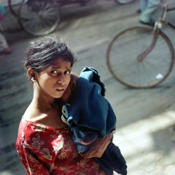 An Indian woman carries her infant child along a busy street in New Delhi, in 2005.