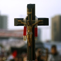 CHRISTIAN PRESENCE. A Christian supporter of pro-democracy actions in Egypt carries a crucifix amid the crowd in Tahrir Square in Cairo Feb. 9. Thousands of pro-democracy demonstrators in the square continued to protest the rule of Egyptian President Hosni Mubarak despite concessions announced by the government.