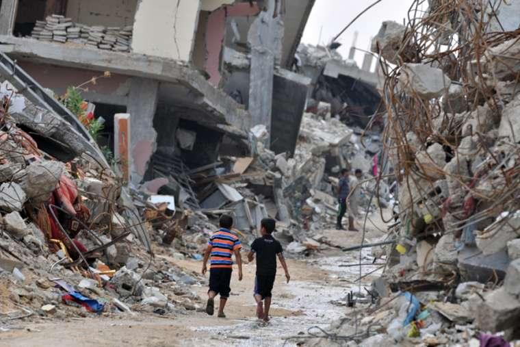 Children amid devastated buildings in Gaza.
