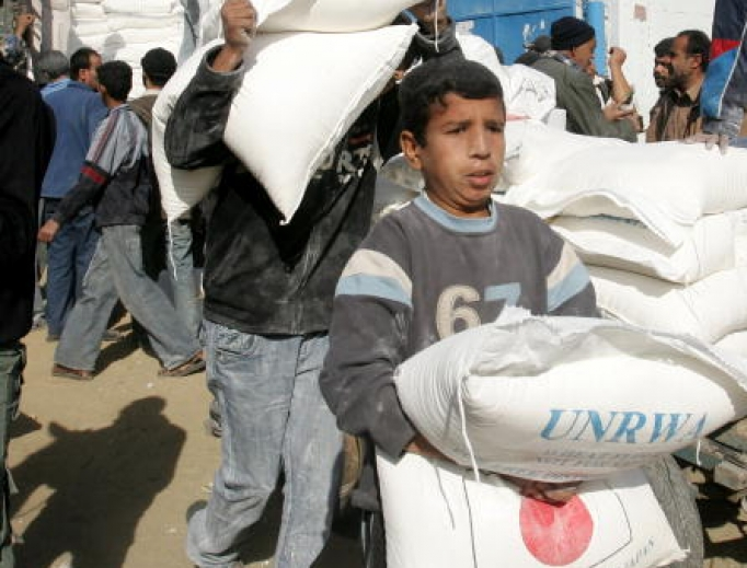 A Palestinian boy helps to unload food aid from the United Nations Relief and Works Agency (UNRWA) in al-Shati refugee camp  in Gaza City, Gaza Strip.