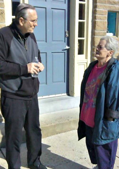 Father Doug McKay talks with a Grays Ferry resident in front of the Matt Talbot House. Below, a Mass is held at Our House Ministries in Philadelphia.
