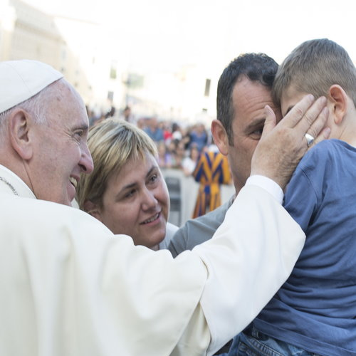 Pope Francis greets a young family after speaking to participants at Rome's diocesan conference about stages of Christian initiation in St. Peter's Square on June 16.