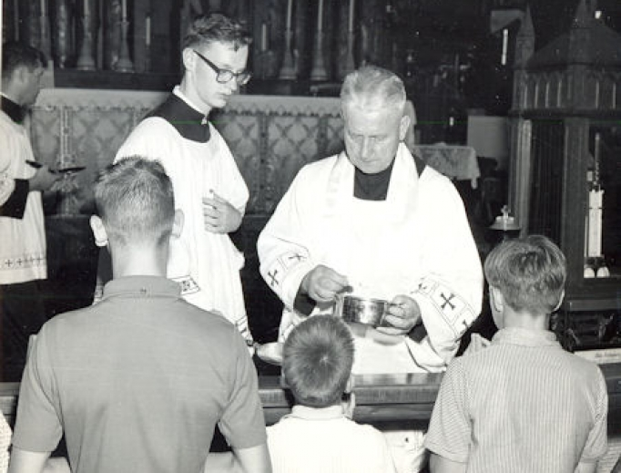 Father Walter Ciszek distributes Communion at Mass in the 1960s.