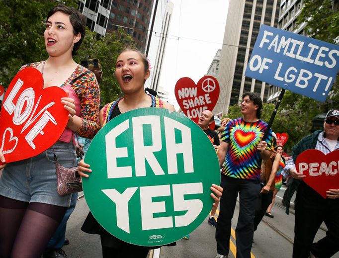 """Pro-Equal Rights Amendment demonstrators march in the annual """"LGBTQI Pride Parade"""" on June 25, 2017 in San Francisco, California."""