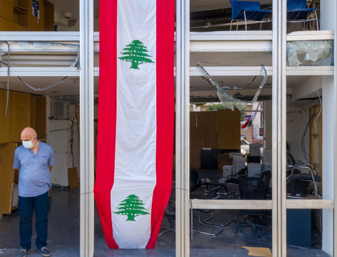 A man stands in the window of a damaged high-rise building, draped with banner in the style of the Lebanese flag, on August 12, 2020 in Beirut, Lebanon. The explosion at Beirut's port last week killed over 200 people, injured thousands, and upended countless lives. There has been little visible support from government agencies to help residents clear debris and help the displaced, although scores of volunteers from around Lebanon have descended on the city to help clean.