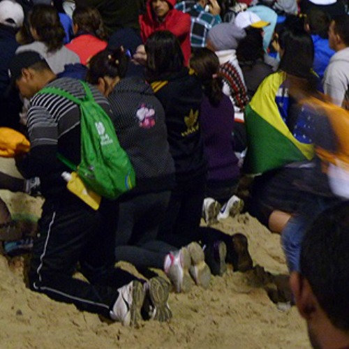 Pilgrims kneel during Stations of the Cross at World Youth Day in Rio de Janeiro, Brazil, July 26, 2013.