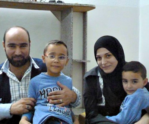 Syrian refugee and Caritas Jordan volunteer Amer Fahd Al Naser, his wife, Noor, and their sons at their apartment in Jordan.