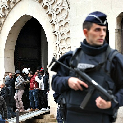 Armed police officers stand outside the Grand Mosque on Jan. 9 in Paris.