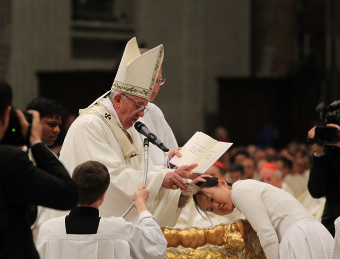 Pope Francis baptizes catechumens during the Easter Vigil Mass at St. Peter's Basilica on March 26, 2016.