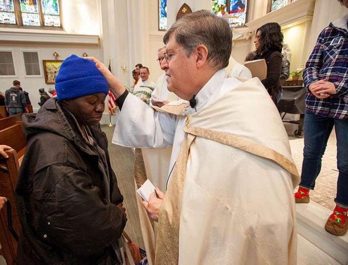 Father Ron Cattany blesses an attendee of the annual Father Woody Christmas cash giveaway, Dec. 14.
