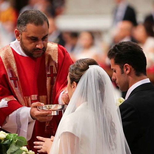 A couple newly married by Pope Francis receives Communion in St. Peter's Basilica on Sept. 14, 2014.