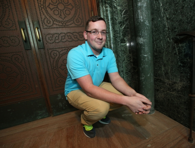 Nathan Leonhardt, a custodian at the Cathedral of St. Paul who found a newborn there Jan. 4, crouches in the spot where he discovered the baby in a laundry basket.