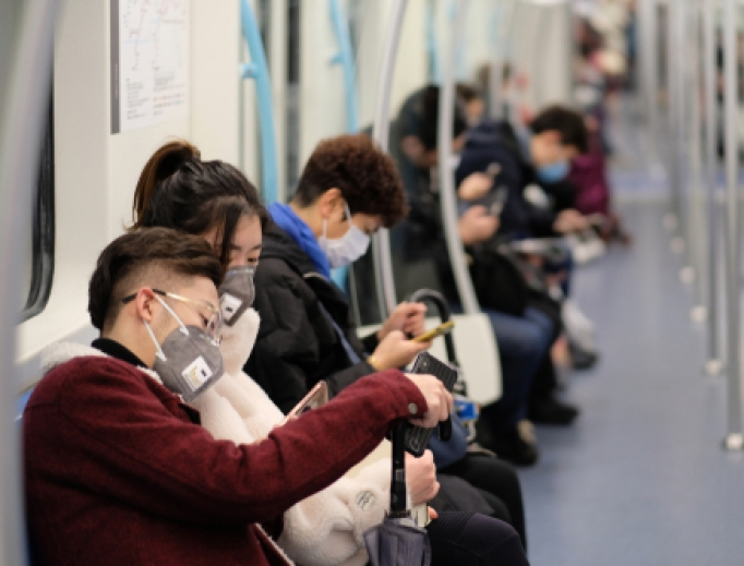 People wearing surgical masks sitting on a subway in Shanghai, January 2020.