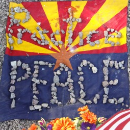 'PRACTICE PEACE.' An Arizona and U.S. flag with stones is seen at the memorial outside the offices of Rep. Gabrielle Giffords in Tucson, Ariz., Jan. 11. Giffords suffered a gunshot wound to the head in a shooting spree that killed six people.