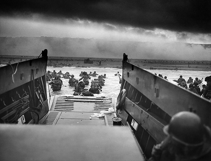A landing craft from the U.S. Coast Guard-manned USS Samuel Chase disembarks troops of Company E, 16th Infantry, 1st Infantry Division (the Big Red One) wading onto Omaha Beach on the morning of June 6, 1944. During the initial landing two-thirds of Company E became casualties.