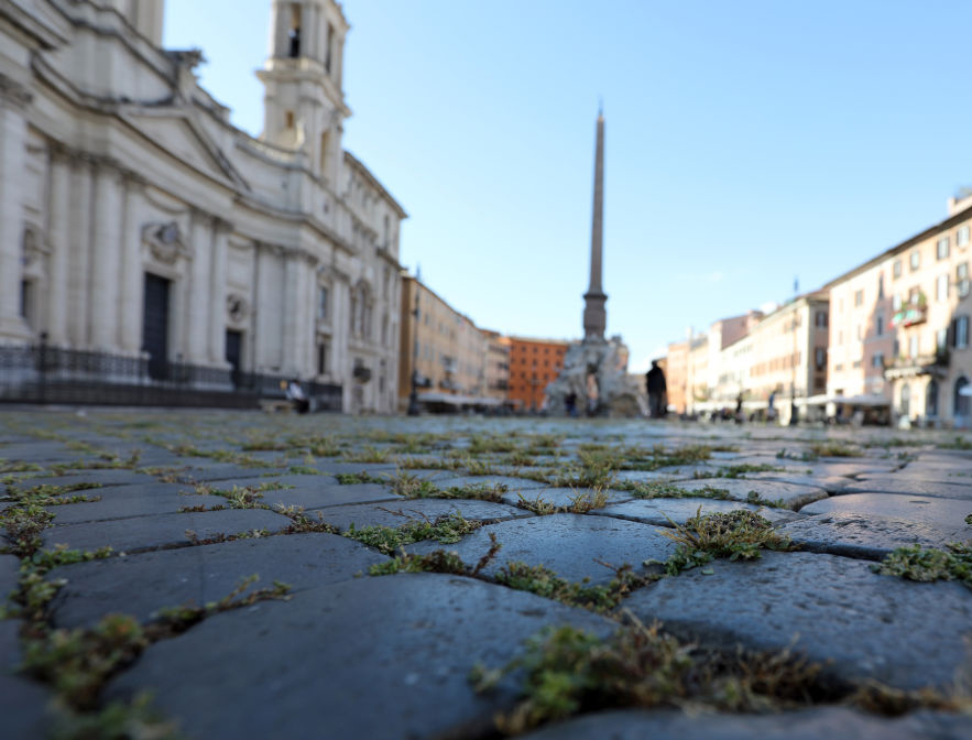 Grass grows between cobblestones (sampietrini) at Piazza Navona Wednesday in Rome. Italy was the first country to impose a nationwide lockdown to stem the transmission of the novel coronavirus and its churches, restaurants, theaters and many other businesses remain closed.