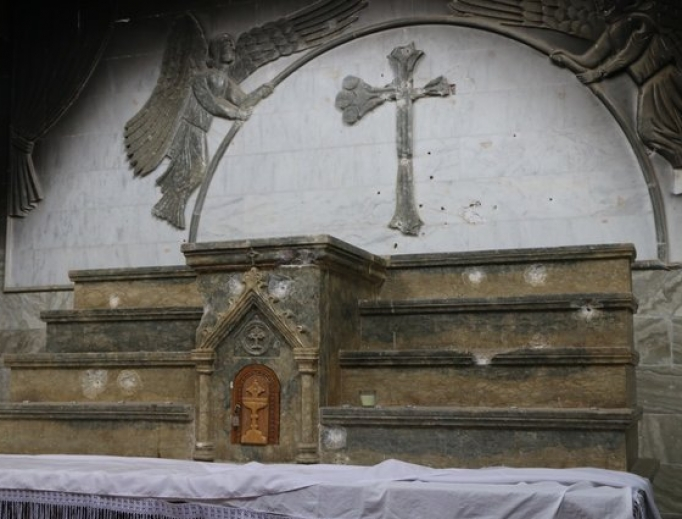 Bullet holes and a defaced cross mar the main altar of St. Addai's Church in Karemlash.