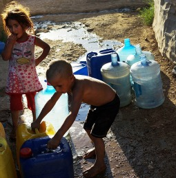 Syrian children fill cans with water June 28 at a Syrian refugee camp in Baalbek, Lebanon.