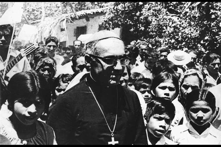 Archbishop Oscar Romero is shown with young people in El Salvador in this undated file photo.