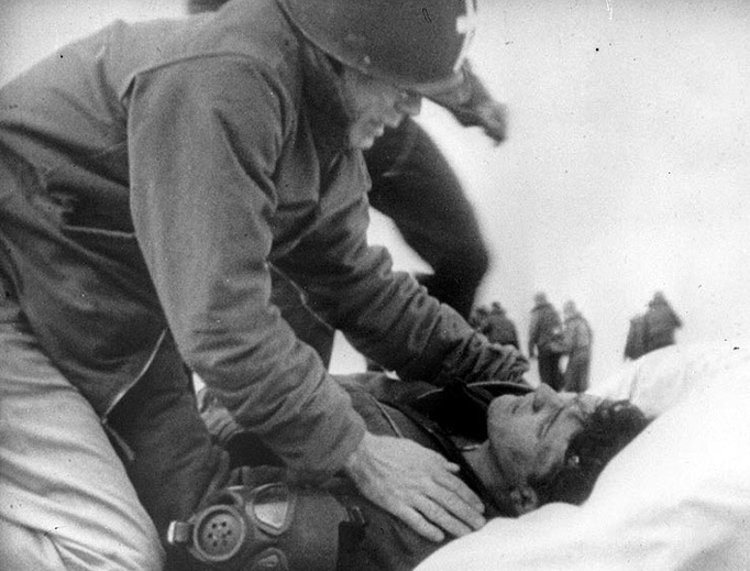 Father Joseph T. O'Callahan serves an injured crewman aboard the USS Franklin (CV-13), after the ship was set afire by a Japanese air attack on March 19, 1945 — the Feast of St. Joseph, the foster father of Jesus.
