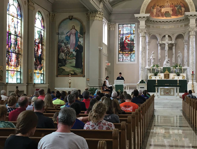 Above, students pray at Mass at St. John's Catholic Newman Center at the University of Illinois. Below, students pray at 'Magnify,' an event that combines praise and worship music with Eucharistic adoration, at St. Mary's Catholic Center at Texas A&M University.