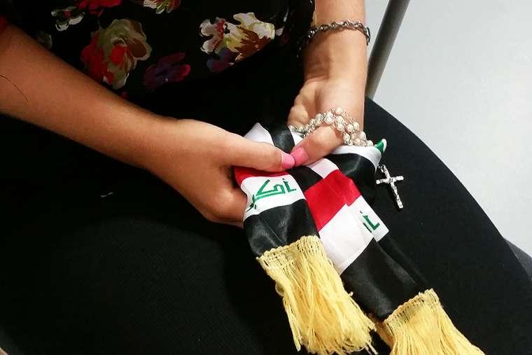 Iraqi woman holding a rosary.