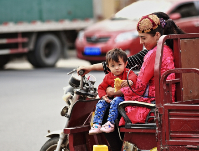Pair of young Uighur women with child ride an auto rickshaw downstreet-Sunday Market's area.