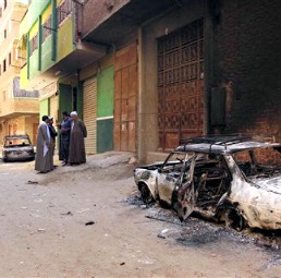 Several burned cars belonging to Egyptian Christians remain in the street after clashes April 6 between Muslims and Christians in a  Cairo suburb.