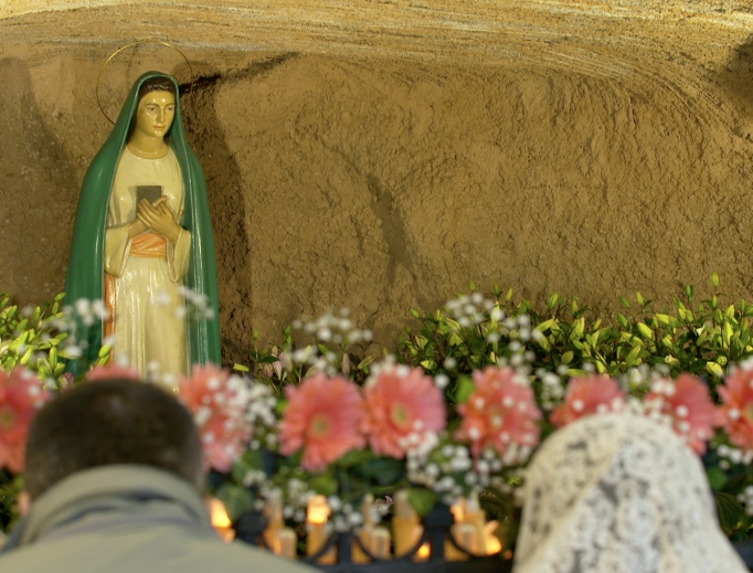 The Tre Fontane Grotto, where Mary appeared in 1947, continuously draws the faithful and inspires conversions, including a reconversion in the life of Bruno Cornacchiola, shown with his family and at the grotto.