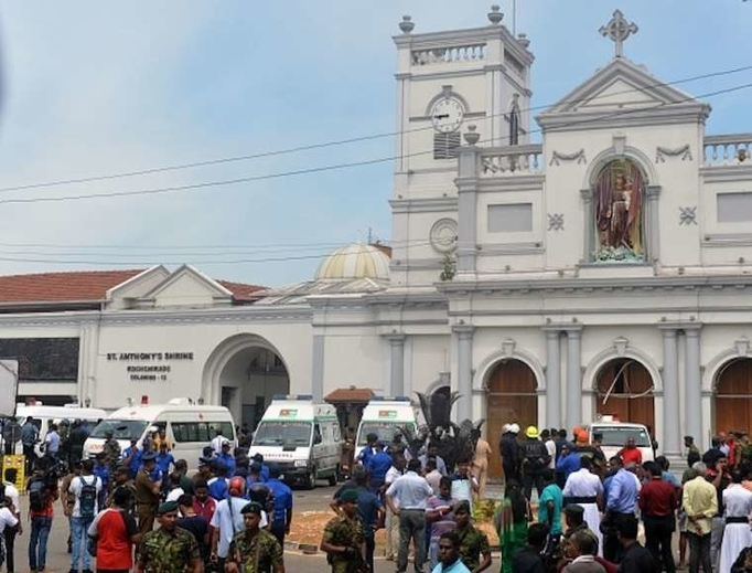 Ambulances are seen outside the church premises with gathered people and security personnel following a blast at the St. Anthony's Shrine in Kochchikade, Colombo on April 21, 2019.