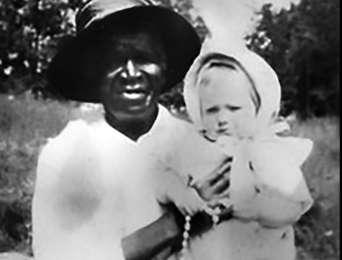 Above, the only photograph of Julia Greeley known to exist shows her holding 7-month-old Marjorie Ann Urquhart. Urquhart's mother told Julia she had lost a child 13 years prior and was told she couldn't have any more children. Greeley prayed for her, and, the next year, Marjorie was born. Below, Archbishop Samuel Aquila signs the oath pledging to fulfill faithfully the task of the cause and blesses the crowd at the Dec. 18 Mass.