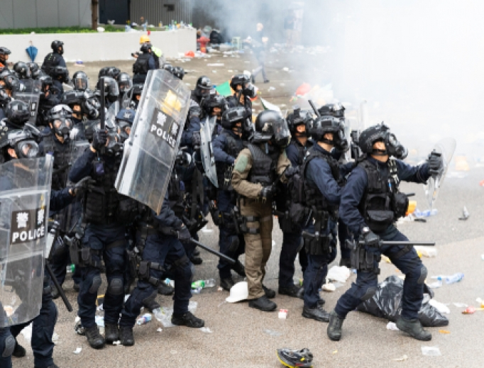 Riot police bunch up next to a cloud of tear gas during clashes with protesters outside the Central Government Office in Hong Kong, June 12, 2019.