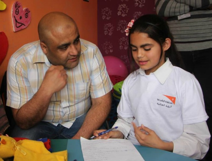 Mohammed Halabi, World Vision's operations manager in Gaza, speaks with a child.