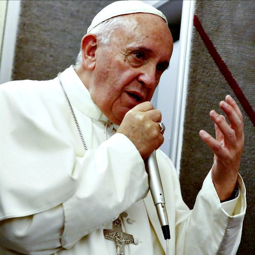 Pope Francis talks to journalists during a press conference he held while en route to Italy on Sept. 28.