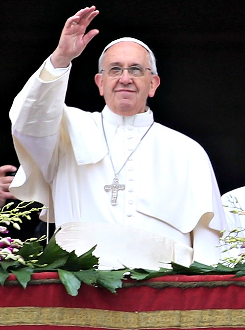 Pope Francis waves to the faithful as he delivers his message and blessing urbi et orbi from the central balcony of St. Peter's Basilica at the end of the Easter Mass.