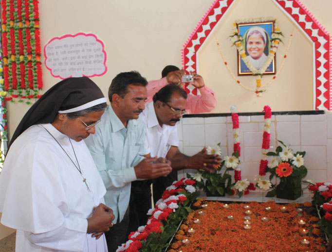 Above, Samandar Singh (center), flanked by Sister Selmy and Stephen, sister and elder brother of Sister Rani Maria, prays at the tomb of Sister Rani on Feb. 25, 2015, the 20th anniversary of her death.