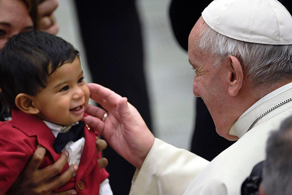 Pope Francis blesses a toddler at the weekly general audience Feb. 12 at the Paul VI Hall in the Vatican.