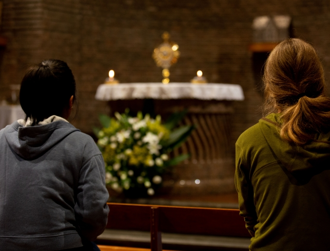 Young people pray for the synod on young people, faith and vocational discernment during Eucharistic adoration at the Centro San Lorenzo in Rome on Oct. 11, 2018.