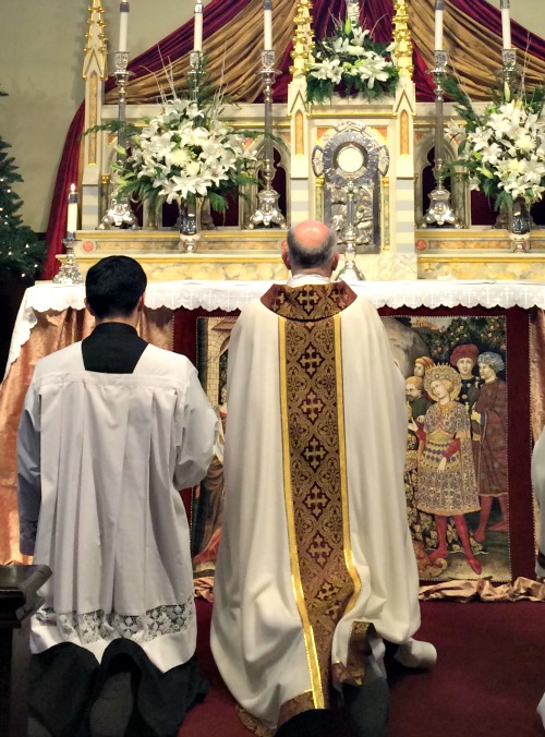 Archbishop Salvatore Cordileone and an altar boy kneel before the Blessed Sacrament at the Church of the Nativity in Menlo Park, Calif.