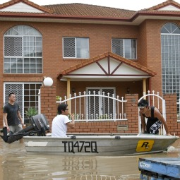 Residents paddle in a boat past a flooded house in Brisbane, Australia, Jan. 13. The flood, which has claimed at least a dozen lives and has affected more than 200,000 people in two dozen towns, is estimated to have already caused nearly $5 billion in damages, devastating much of Australia's coal, beef and agriculture industries.