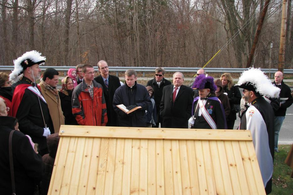 Donald Creatore in red tie stands to the right side as his pastor blesses the creche on town hall green.