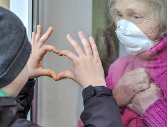 A grandmother in a respiratory mask communicates with her grandchild through a window amid the coronavirus pandemic.